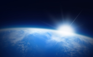 blue earth with rising sun seen from space