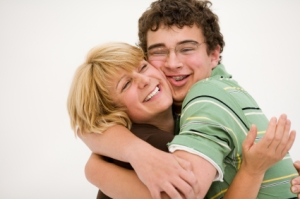Mother hugging teen son after resolving conflict.